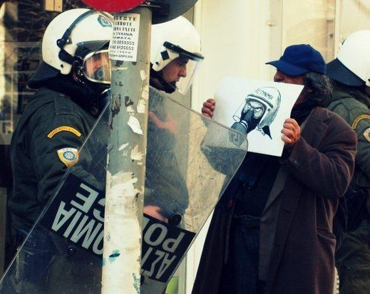 Man defies a cop with a Latuff cartoon Athens Greece January 12 2013